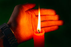 Red candle and hand. Lone red candle shining brightly Stock Images