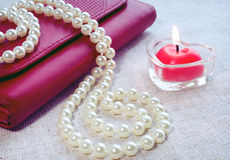 Red candle,  handbag  and pearl Stock Photos