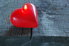 Red heart shape candle on old wood Royalty Free Stock Photos