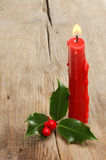 Red candle and holly Royalty Free Stock Image