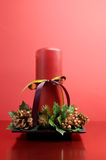 Red candle with holly and pine cone Christmas table centrepiece still life Royalty Free Stock Photography