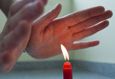 Red candle and human hands Stock Photos