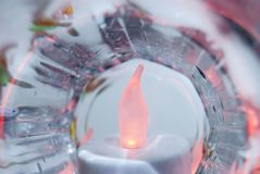 Red candle inside of glass cup with water drops and colorful reflections royalty free stock image
