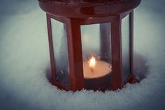 Red candle lantern with candle in snow Stock Image