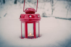 Red candle lantern with candle in snow Royalty Free Stock Photos