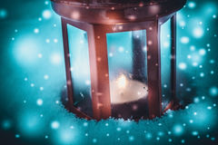 Red candle lantern with candle in snow during snowfall Stock Photo