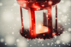 Red candle lantern with candle in snow during snowfall Royalty Free Stock Photography