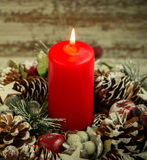 Red candle lit and pinecones for Christmas Stock Photography