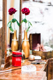 Red candle on a mirror. On a background of red roses in a gilded bottle stock photography