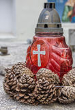 Red candle and pine cones on a marble grave in Brasov Royalty Free Stock Image