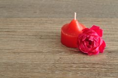 Red candle with a pink rose. A red candle with a pink rose Royalty Free Stock Images