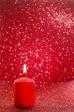 Red candle. Red glittering christmas lights. Blurred abstract ba Royalty Free Stock Images