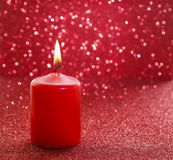 Red candle. Red glittering christmas lights. Royalty Free Stock Photo
