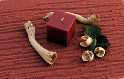 Red candle on the sand with sticks and flowers. Concept of wellness Royalty Free Stock Photos
