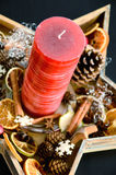Red candle with with scattered christmas spices and deco elements Royalty Free Stock Photo