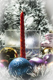 Red candle, silver tinsel and blue,gold balls Royalty Free Stock Images