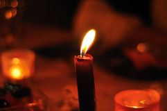 Red candle. Spreading soft and warm light Royalty Free Stock Photos