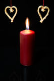Red candle and straw hearts on black background. Copyspace Stock Photo