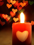 Red candle on the table and shiny hearts in background. Royalty Free Stock Images