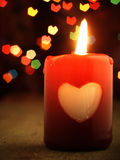 Red candle on the table and shiny hearts in background. Stock Photos