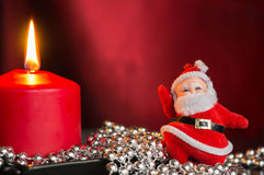 Red candle with a toy Santa Claus Royalty Free Stock Photo