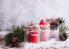 Red candle, twigs and cones on a snow-covered wooden background Royalty Free Stock Photo