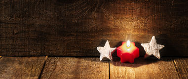 Red candle and white stars on wooden background with copy space. Royalty Free Stock Images