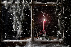 Red Candle in Window. A burning red candle inside window at night with falling snow and evergreen branches on outside Stock Photography