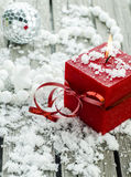 Red candle on a wooden table. In the snow Stock Images