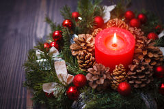 Red candle in a wreath of pine branches with Christmas balls Stock Photo