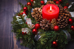 Red candle in a wreath of pine branches with Christmas balls Stock Image