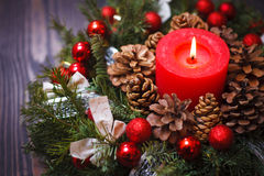 Red candle in a wreath of pine branches with Christmas balls Royalty Free Stock Image