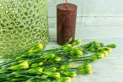 Red candle with yellow carnations stock image