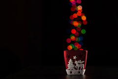 Red candleholder with christmas lights in background Royalty Free Stock Photos