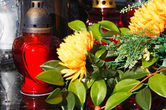 Red candles and artificial flowers on a grave Stock Images