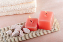 Red candles on bamboo mat. Red candles and pebbles on bamboo mat Royalty Free Stock Photo