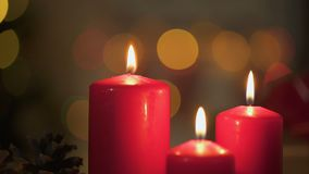 Red candles burning, Christmas lights twinkling on background, miraculous time. Stock footage stock video