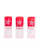 3 red candles, candle holders with crystal snowflakes isolated on reflective white perspex background Stock Photography