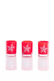 3 red candles, candle holders with crystal snowflakes isolated on reflective white perspex background with copy space Royalty Free Stock Photo