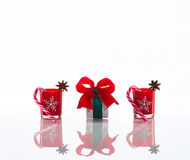 Red candles, candle holders with crystal snowflakes, sugar canes and anise stars and a gift box, isolated on reflective white pers Royalty Free Stock Photos