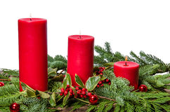Red candles with cedar boughs and holly Royalty Free Stock Images