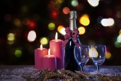 Red candles and champagne bottle over snow stock photo