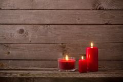 Red candles on dark wooden background Stock Photo
