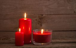 Red candles on dark wooden background Stock Images