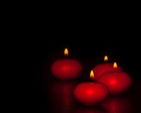 Red candles with flame on wood and black background, dark atmospere Stock Images