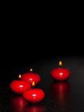 Red candles with flame on wood and black background Royalty Free Stock Images