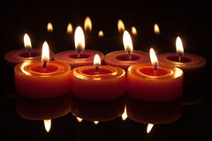 Red candles with flames on a dark background. Glowing flames from candles with reflections top and bottom royalty free stock photography