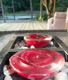 Red Candles in  Glass. Two red candles in round shaped glass within square black wooden table decoration surrounded  by white rocks Royalty Free Stock Photography