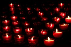 Red candles with glowing lights in darkness in church. Peace and hope background. Religion concept. Red candles with glowing lights in darkness in church stock photos