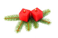 Red candles and green pine needles. On white background, soft shadows Royalty Free Stock Images